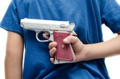 Petit garçon prenant à arme à feu derrière le sien le dos dangereux Images libres de droits