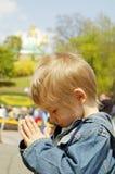 Petit garçon priant à l'extérieur Photographie stock libre de droits