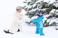 Petit garçon préscolaire et sa mère jouant avec la première neige dans p Photos stock