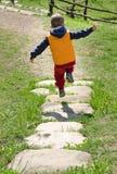 Petit garçon sautant le long d'un sentier piéton en pierre Photographie stock