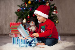 Petit garçon sur Noël, présents s'ouvrants Photos stock