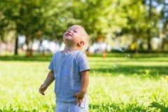 Petit gentil garçon appréciant un jour merveilleux dans le jardin photo stock