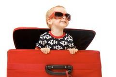Petit gosse dans des lunettes de soleil regardant à l'extérieur la valise rouge Images libres de droits