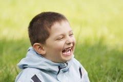Petit gosse riant dans l'herbe Photographie stock libre de droits