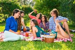 Petit groupe d'amis mangeant des raisins sur une couverture Photo stock