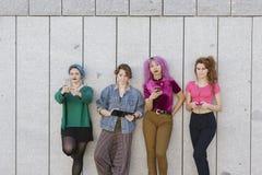 Petit groupe de femmes de l'adolescence avec la technologie d'isolement contre un gre Images stock