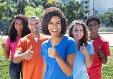 Petit groupe de jeune homme heureux et de femme montrant le pouce  Photographie stock libre de droits
