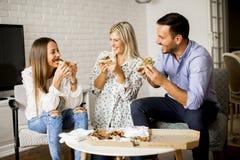 Petit groupe de jeunes amis mangeant de la pizza dans la chambre Photos libres de droits