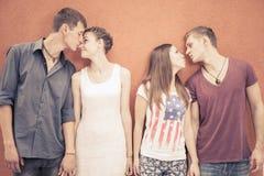 Petit groupe de personnes embrassant, se tenant près du fond rouge de mur Photo libre de droits