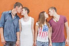 Petit groupe de personnes embrassant, se tenant près du fond rouge de mur Photographie stock libre de droits