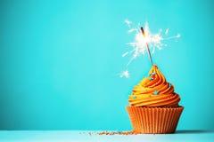 Petit gâteau orange avec le cierge magique Images libres de droits