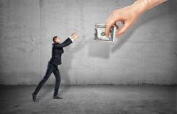 Petit homme d'affaires sur le fond concret atteignant pour une main géante tenant l'argent Photos stock
