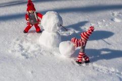Petit homme deux en bois dans la scène de construire un bonhomme de neige parmi le Th Photographie stock libre de droits