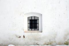 Petit hublot dans le mur de la vieille prison Photo stock