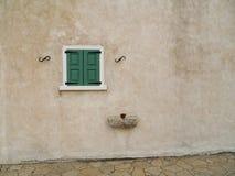 Petit hublot vert sur le mur en pierre ordinaire Image stock