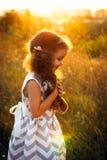 Petit hugd bouclé mignon de fille un hibou pelucheux de jouet Jeu de fille d'enfant en bas âge avec la poupée douce Une belle lum Photographie stock libre de droits