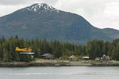 Petit hydravion jaune volant plus d'et débarquant dans la petite ville Image libre de droits