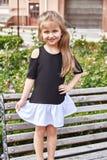 Petit jeu de petite fille sur le support de cour de yard sur le banc Photographie stock libre de droits