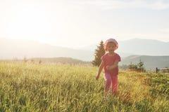 Petit jeu heureux mignon de bébé dehors pendant le début de la matinée dans la pelouse et le Mountain View admiratif Copiez l'esp Photos stock