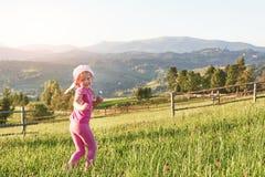 Petit jeu heureux mignon de bébé dehors pendant le début de la matinée dans la pelouse et le Mountain View admiratif Copiez l'esp Image libre de droits