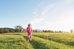 Petit jeu heureux mignon de bébé dehors pendant le début de la matinée dans la pelouse et le Mountain View admiratif Copiez l'esp Photographie stock libre de droits