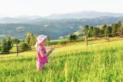 Petit jeu heureux mignon de bébé dehors pendant le début de la matinée dans la pelouse et le Mountain View admiratif Copiez l'esp Photos libres de droits