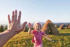 Petit jeu heureux mignon de bébé dehors pendant le début de la matinée dans la pelouse et le Mountain View admiratif Copiez l'esp Images libres de droits