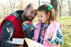 Petit jolis enfant et père affichant le livre Images libres de droits