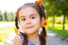 Petit kazakh adorable, fille asiatique d'enfant sur le fond de nature de vert d'été Photographie stock