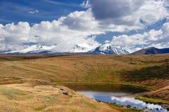 Petit lac rond des montagnes sur le fond des crêtes de montagne élevées de neige Image libre de droits