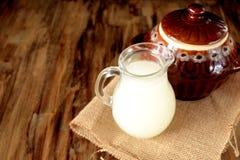 Petit lait de lait dans une cruche en verre et un pot d'argile photographie stock libre de droits
