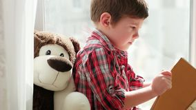 Petit livre de lecture d'enfant à la maison, enfant futé s'asseyant sur la fenêtre avec la fourrure à et lisant des contes de fée banque de vidéos