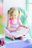 Petit livre de lecture drôle de fille près de fenêtre Photographie stock