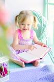 Petit livre de lecture drôle de fille près de fenêtre Photographie stock libre de droits