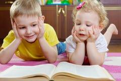 Petit livre de lecture mignon de frère et de soeur sur le plancher Photographie stock libre de droits
