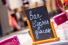 Petit menu noir de conseil indiquant la barre, les glaces et les crêpes (crêpes Glaces de barre en français) sur une table dehors Image libre de droits
