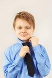 Petit monsieur mignon attachant le sien au-dessus de la chemise lumineuse Images stock