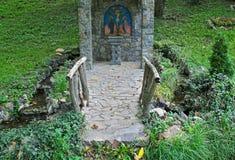 Petit monument chrétien en pierre décoré en parc image stock