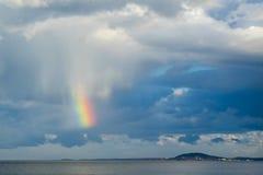 Petit morceau d'arc-en-ciel au-dessus de mer contre le ciel nuageux Photos libres de droits