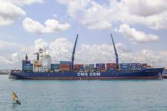 Petit navire et navire porte-conteneurs énorme, port de la ville en pierre photos libres de droits