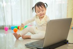 Petit ordinateur portable asiatique de jeu de fille dans la maison Photographie stock