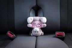 Petit ours de nounours se tenant sur sa tête sur un siège de voiture images libres de droits