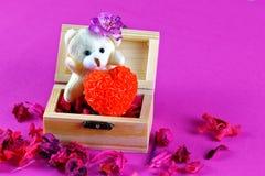 Petit ours de nounours tenant l'amour dans la boîte en bois Photo libre de droits