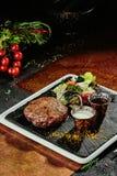 Petit pâté grillé de viande avec de la salade et deux sauces d'un plat noir sur un fond de cuivre Plan rapproché photos libres de droits
