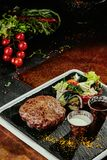 Petit pâté grillé de viande avec de la salade et deux sauces d'un plat noir sur un fond de cuivre Plan rapproché photo libre de droits