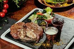 Petit pâté grillé de viande avec de la salade et deux sauces d'un plat noir sur un fond de cuivre Plan rapproché images libres de droits