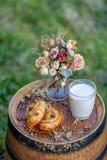 Petit pain avec des raisins secs et un verre de lait sur le vieux baril de vin Dessert Bouquet des fleurs d?fra?chies photographie stock libre de droits