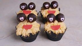 Petit pain avec des yeux de chocolat et le sourire rouge Concept de Veille de la toussaint Monstre doux banque de vidéos