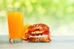 Petit pain bourré avec le jus d'orange sur la table, chrono- concept de régime Photographie stock libre de droits