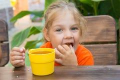 Petit pain bourré drôle de fille de quatre ans dans sa bouche Photo libre de droits